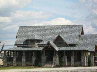 A log cabin home in Tennessee selected EDCO's Arrowline Slate Roofing in Charcoal Gray Blend  to complement the rustic look of the homes wood and stone.