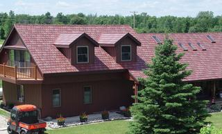 Arrowline Slate Roofing in a Classic Red Blend was installed on this rural farmhouse to not only match the color of other buildings but to give the home unique character.