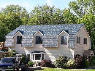 The beauty of this unique home can be found with its ArrowLine Hartford Green Enhanced Slate Roofing.