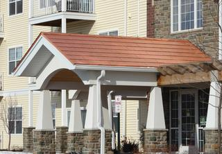 The covering of the entrance to an apartment complex showcases the Arrowline Shake Copper Roofing to bring out the rich colors of the stone and brick installed on the building.